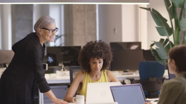 female business colleagues discussing at office - mixed race person stock videos & royalty-free footage