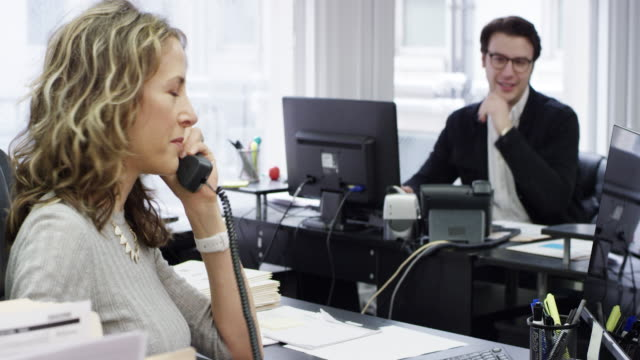 Female business esecutive and young business man with glasses working together in the back office of a brand