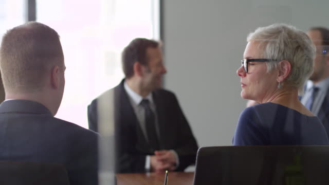 MS Female business executive listening to colleagues during meeting in conference room