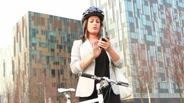 Weibliche Geschäftsmann am Telefon, die mit dem Fahrrad außerhalb Büro
