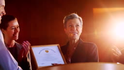 Female business executive receiving award