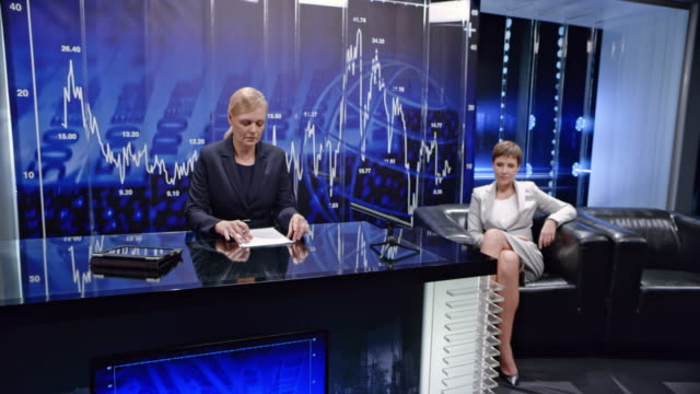 CS Female business news host welcoming viewers as the lights turn on in the studio