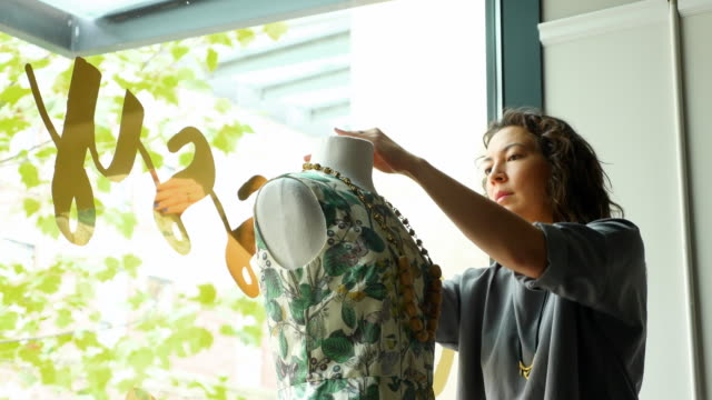 vidéos et rushes de ms female business owner dressing dress form in window of boutique - entreprise