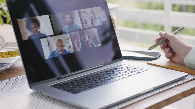 female business owner making notes in front of laptop showing virtual team meeting - medium group of people stock videos & royalty-free footage