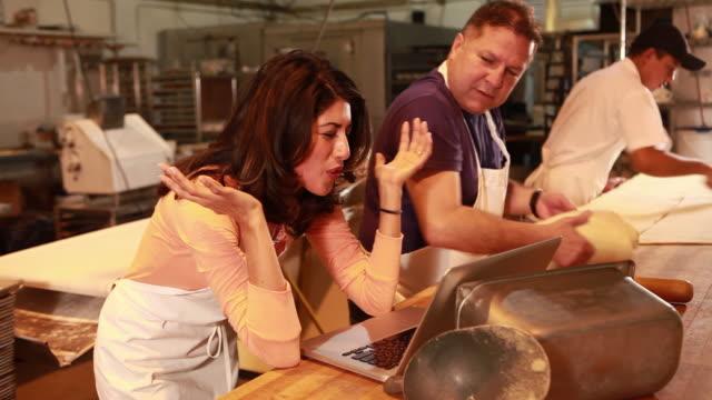 vídeos y material grabado en eventos de stock de ms female business owner working on her laptop in bakery / sante fe, new mexico, usa - mano en la barbilla