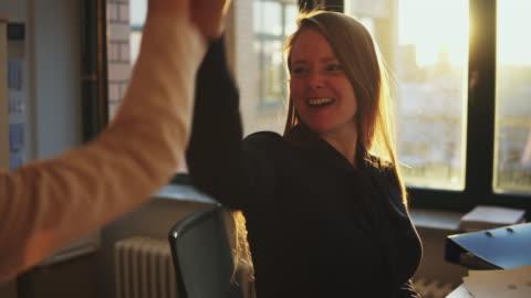 vidéos et rushes de female business owners high-fiving in office. - motivation