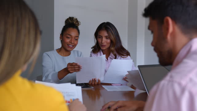 female business partners discussing something while looking at some documents during a board meeting - smart casual stock videos & royalty-free footage