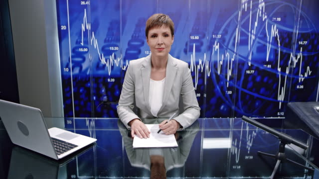 CS Female business talk show host doing the concluding speech and shaking hands with guest as the lights go out