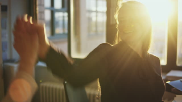 vidéos et rushes de female business women doing high-five in office. - only women