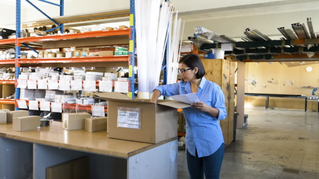 vidéos et rushes de female businesswoman checking delivery in a small business - expertise
