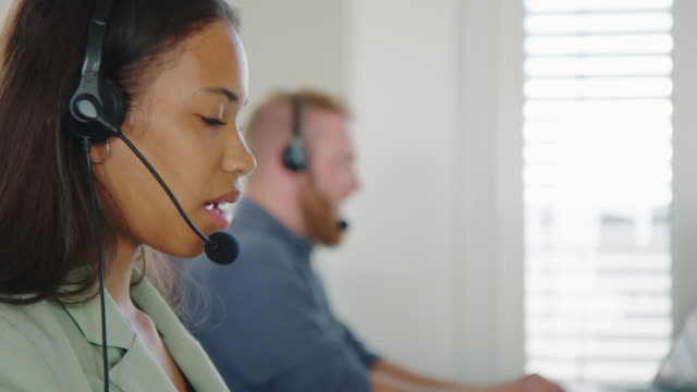 female call center agent working at her desk - outsourcing stock videos & royalty-free footage