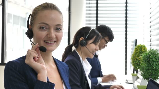 female call center operator talking with her customer and looking at camera - telecommunications equipment stock videos and b-roll footage