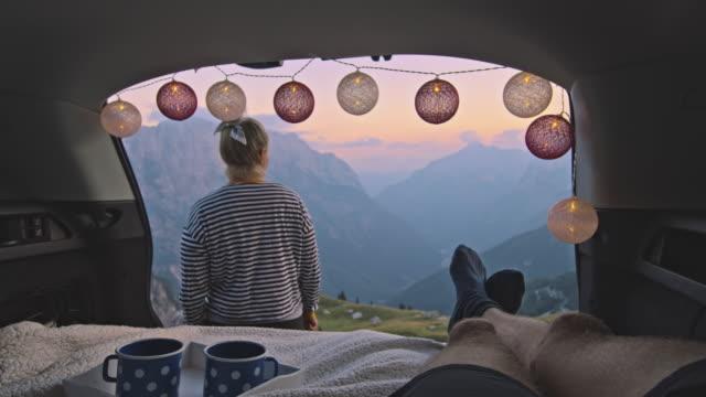 slo mo weibliche camper in der genießen des sonnenuntergangs vor ihrem partner - travel destinations stock-videos und b-roll-filmmaterial