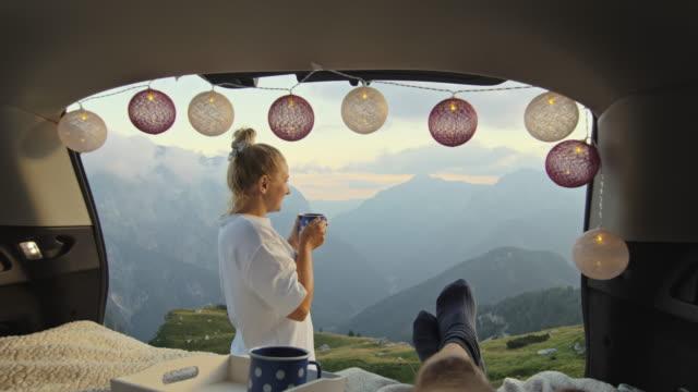 slo mo weibliche camper machen morgen strecke vor ihrem partner und genießen den morgenkaffee in den bergen - fairy lights stock-videos und b-roll-filmmaterial