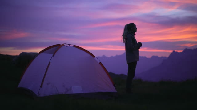 female camping solo standing in front of tent watching sunset - tent stock videos & royalty-free footage