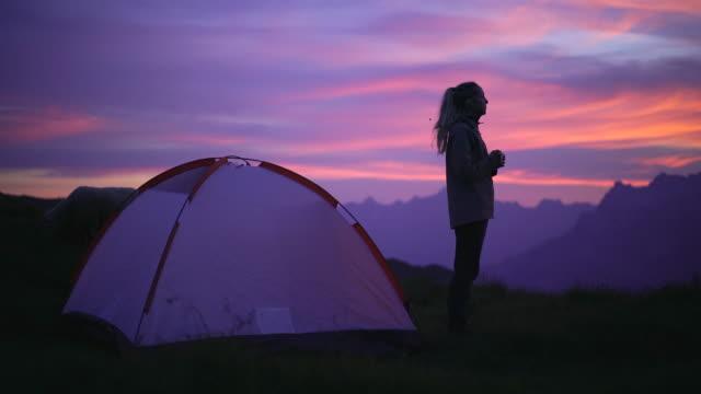 stockvideo's en b-roll-footage met vrouwelijke camping solo staand voor tent kijken zonsondergang - tent