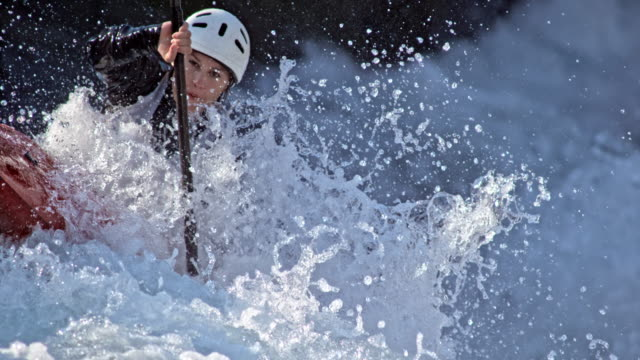 slo mo female canoeist battling the whitewater on a slalom course - 急流点の映像素材/bロール