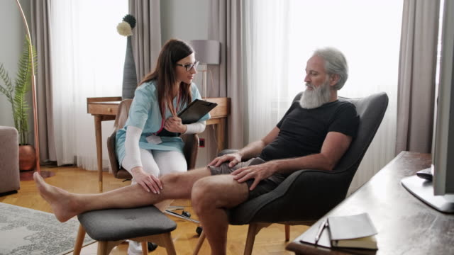 female caregiver talking to mature man in living room - recovery stock videos & royalty-free footage