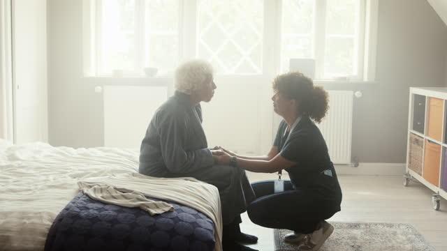 female caregiver talking with senior woman - bathrobe stock videos & royalty-free footage