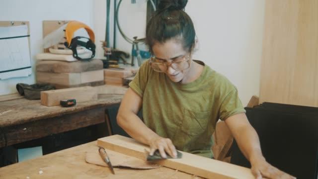 carta vetrata da falegname femminile (slow motion) - carpenteria video stock e b–roll