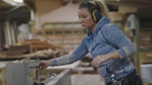 female carpenter wearing ear protectors holding plank on machinery at workshop - skakig kamerabild bildbanksvideor och videomaterial från bakom kulisserna