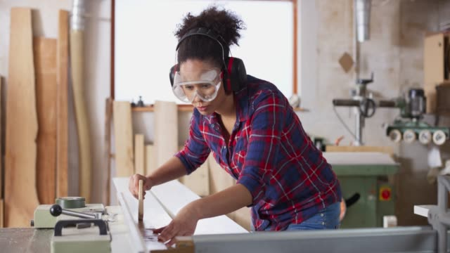 ds female carpenter wearing eye and ear protection cutting planks on the table saw in her workshop - carpentry stock videos & royalty-free footage