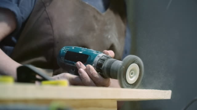 Female carpenter working with angle grinder