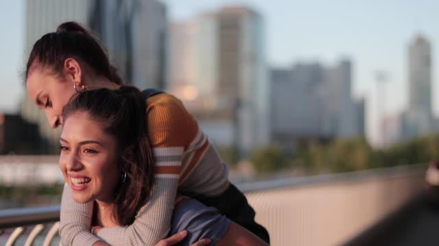 female carrying girlfriend on shoulder in city - huckepack nehmen stock-videos und b-roll-filmmaterial