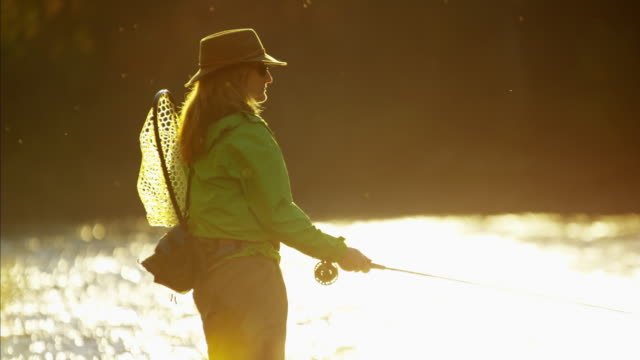 Female casting line in freshwater river sunrise USA