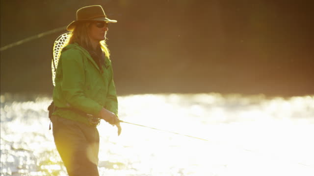 stockvideo's en b-roll-footage met female casting line in freshwater river sunrise usa - hengel uitwerpen