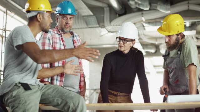 ds 白人女性建築家の電気技師、大工、ブルドーザーのオペレーターと計画を議論 - 発電所関係の職業点の映像素材/bロール