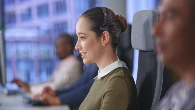 vídeos de stock, filmes e b-roll de agente caucasiano fêmea do centro de chamadas de ld que fala com um cliente nos escritórios do centro de chamadas - coque cabelo para cima