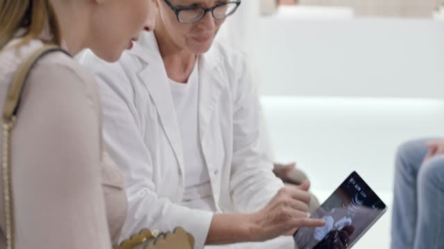 weiblichen kaukasischen ob-gyn erklärt ultraschall fotodetails schwangere patienten im wartezimmer - patientin stock-videos und b-roll-filmmaterial