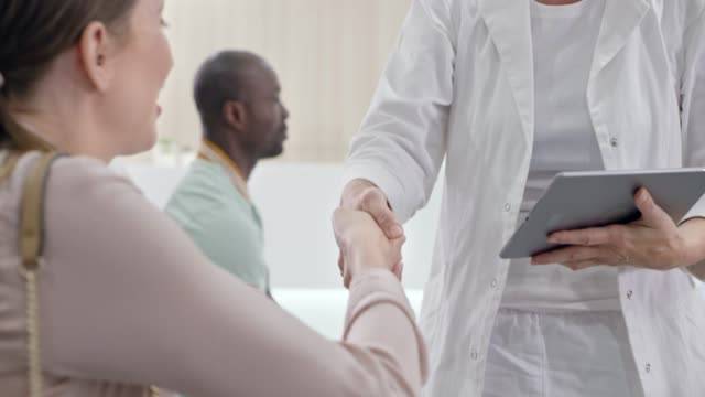 female caucasian ob-gyn shaking hands with the female patient she talked to in the waiting room - sala d'attesa video stock e b–roll