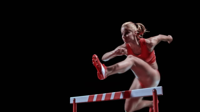 SLO MO LD Female Caucasian sprinter jumping over a hurdle