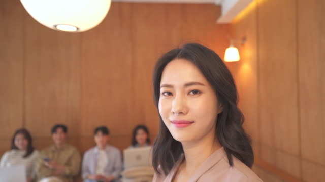 female ceo and young people smiling big in a lounge, startup business - 人間の鼻点の映像素材/bロール
