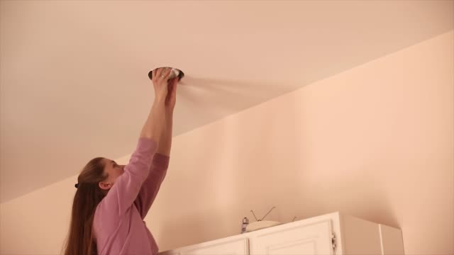 female changes a recessed light fixture in ceiling at home - cupboard stock videos & royalty-free footage