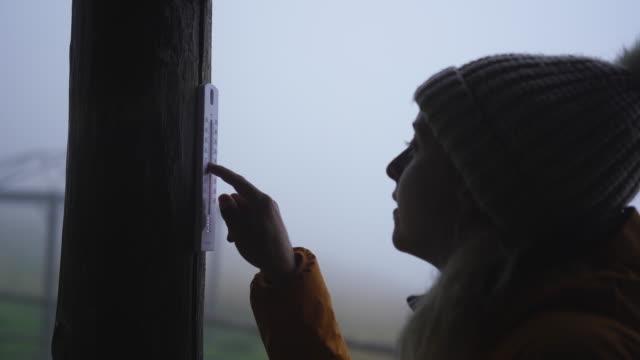 vídeos de stock e filmes b-roll de female checks temperature on thermometer outside stone hut - cold temperature