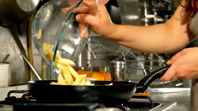 female chef cooking pasta with chicken and mushrooms - close up - stirring stock videos & royalty-free footage