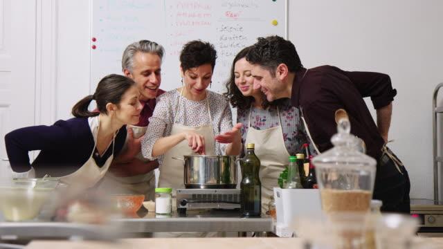weibliche köchin koch pasta mit studenten stehen - haushaltsmaschine stock-videos und b-roll-filmmaterial