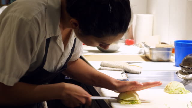 vidéos et rushes de ms r/f female chef dicing fennel in preparation for evening meal service in restaurant kitchen - chemise