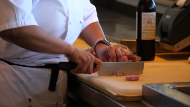 vídeos de stock, filmes e b-roll de ms female chef dicing shallot while preparing for dinner service in restaurant kitchen - controlo de qualidade