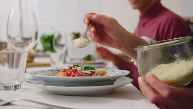 female chef garnishing pasta with grated cheese at dining table - grated stock videos & royalty-free footage