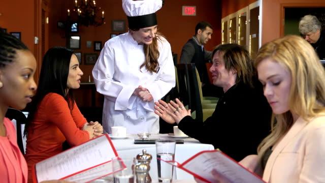 weibliche küchenchef begrüßt gäste im geschäftigen restaurant - gastwirt stock-videos und b-roll-filmmaterial