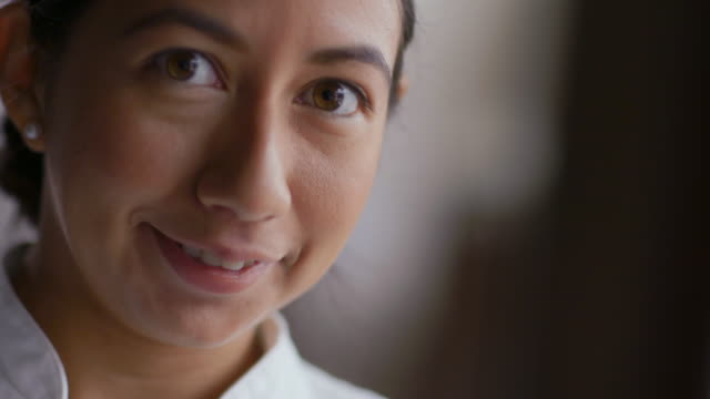 female chef looks up and smiles at camera - gourmet küche stock-videos und b-roll-filmmaterial