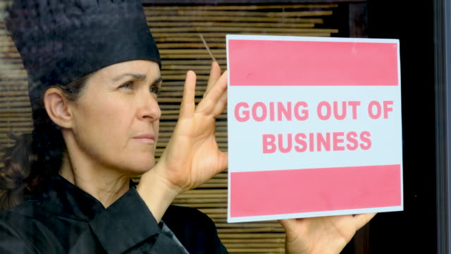 female chef posting a going out of business sign at her restaurant window - closed sign stock videos & royalty-free footage