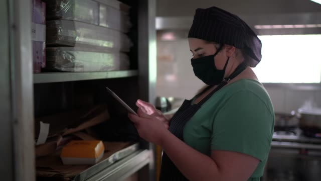 female chef preparing food and using digital tablet in an industrial kitchen with face mask - quality control stock videos & royalty-free footage