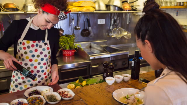 MS female chef preparing food in restaurant kitchen for customer