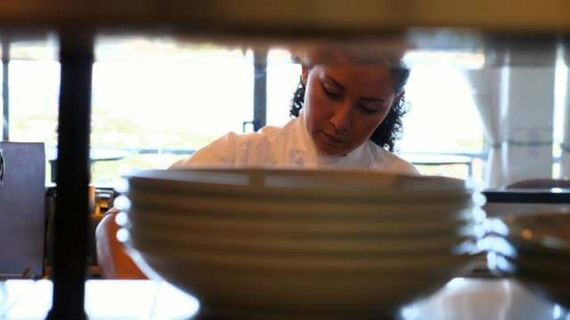 vidéos et rushes de cu female chef preparing food in restaurant kitchen - latino américain