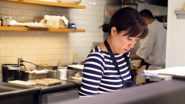 ms female chef preparing for evening meal service at counter in restaurant kitchen - kitchen worktop stock videos and b-roll footage
